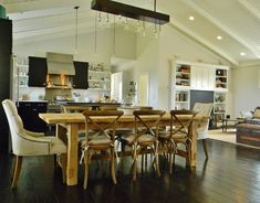 open concept living - dining area with rustic farmhouse table mixed with x-back French bistro chairs and upholsters head chairs