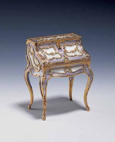 This Louis XV-style miniature roll-top desk was originally purchased by Leopold de Rothschild from Fabergé's London branch on 12 July 1908 for £150.15s (£150.75). Crafted from two-colour gold and embellished with mauve guilloché enamel, it opens with a miniature gold key, revealing an interior lined with engraved mother-of-pearl that divides it into compartments. King George VI acquired the piece for his wife Queen Elizabeth in 1946.