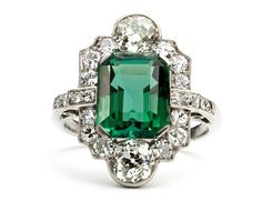 Art Deco Green Tourmaline Cocktail Ring This stunning Art Deco platinum ring circa 1920, will have everyone guessing you are wearing an emerald! The 3.37ct tourmaline has a rich green color, and cushion shaped old mine diamonds above and below the gemstone, give the ring its interesting shape. Another twenty other diamonds set off the lush green color with dazzling sparkle.