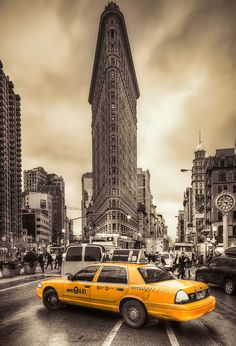 Another image of a new york taxi and land mark Flat Iron Building. Again the image is black and white with the yellow taxi pulled out and focused in only colour. - KW