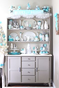 Add some holiday decor to your kitchen hutch with metallic blue and silver ornaments and white bottlebrush Christmas trees.