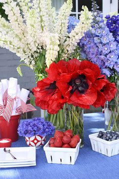 There are white Lupins, Blue Delphinium, Red Poppies, Red Sweetpeas, and Blue Bachelors Buttons (sometimes called cornflowers).