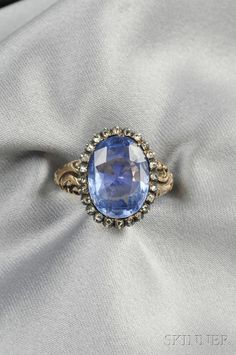 Antique Sapphire and Diamond Ring, set with a cushion-cut sapphire measuring approx. 14.00 x 10.00 x 6.58 mm, and weighing approx. 7.50 cts., framed by rose-cut diamonds, silver and 14kt gold mount, size 6 3/4. Georgian or Georgian style.