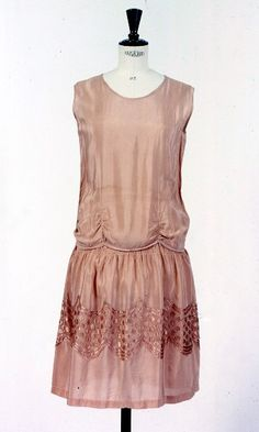 Dress ca 1928  A peach evening dress made of rayon trimmed with a wide band of light gold shiny rayon lace.