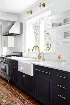 Dark navy island with Calcutta gold   Creamy white cabinets around perimeter with grey countertops