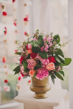 Using coral and pink florals for an altar arrangement for the wedding ceremony