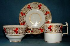 """This is a Derby (Mid Bloor Period) porcelain trio consisting of a tea cup, coffee can and saucer c.1806-25.   It is in the """"London shape"""".  It is decorated in pattern no. 19, a lovely floral leaf and vine pattern and rich gilding.  The Derby red mark (Painted mark with Crown above crossed batons and D below) is on the cup and the can.  Provenance: Marc-James Museum DO293."""