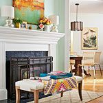 love the mantel - two short shiny lamps, flowers, and art work