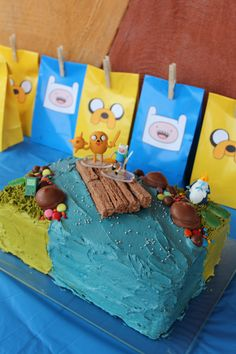 Adventure Time cake and loot bags - Rainbow vanilla cake inside with buttercream icing and lolly/biscuit decorations. Figurines are toys on a Cadbury Flake raft.