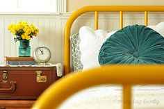 iron bed frame- love this yellow with the teal. LOVE the velvet pillow and suitcases by the bed. Painted Iron Beds, Painted Bed Frames, Painted Metal, Painted Headboard, Brass Headboard, Master Bedroom Design, Home Bedroom, Bedroom Decor, Tan Bedroom