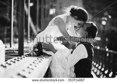 Young beautiful stylish fun pair of newlyweds on a bridge in Budapest, Hungary. Beautiful woman in a white wedding dress and handsome man in the three-piece suit.
