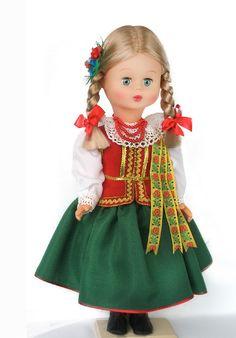 Strój Łańcucki  strój kobiecy: biała bluzka, zielona spódnica wykończona u dołu czerwoną wypustką, czerwony gorset ze złotymi zdobieniami, do lewego ramienia przyczepione haftowane wstążki, włosy zaplecione w jeden warkocz, przyozdobiony wstążką i kwiatami. W ręku ozdobna chusteczka. Pracownia Lalek Regionalnych FOLKLOR