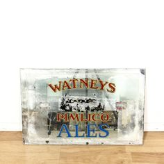 """This vintage """"Watneys Pimlico Ales"""" sign mirror is featured in a durable glass with a distressed finish. This accent mirror sign has etched trim with unfinished edges and painted words. Perfect for decorating an empty wall! #americantraditional #decor #mirror #sandiegovintage #vintagefurniture"""