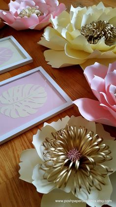 Baby pink, cream and gold paper flowers.  This listing includes 1 x- large flower - 21 inches 2 medium flowers - 14 inches 2 small flowers 10 inches 4 leaves OPTIONAL 2 framed monstera leaves - 8 by 10 inches  Can be made in any size or color  Each flower is individually designed and custom made. Each flower may slightly vary in design since it is custom made. Our Paper flowers can also be customized with business logos, names, dates etc. ------Installation------- Our paper flowers come with…