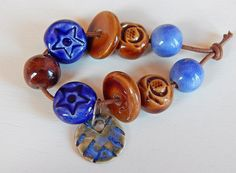 The set consists of = 7 beads , 2 discs and 1 charm of porcelain and stoneware ,hand carved ,have blue and brown glazes , the smaller bead measures 12 x 12 mm. and the largest 15 x 15 mm. , the discs measures 18 x 18 mm. and the charm measures 20 x 20 mm. By Mª Carmen Rodriguez Martinez ( Majoyoal ) https://www.facebook.com/groups/CeramicArtBeadMarket/