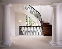 Iron stair railing and wood stairs become the focal point of this luminous stairhall, boldly contrasting an otherwise light color palette. Staircase Railing Design, Iron Stair Railing, Stair Banister, Curved Staircase, Dream House Interior, Interior Stairs, Home Room Design, House Design, Modern Entrance Door