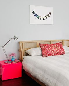 "Little girl's room with vibrant bedside table and ""whatever"" art above bed"