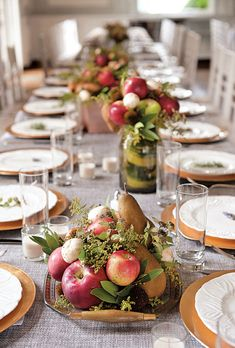 Wedding centerpiece of locally grown apples, pears, peaches, and mushrooms accented with sprigs of mint, bay leaves, echinacea, and moss, displayed on vintage trays