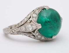 Edwardian Cabochon Emerald Ring. Magnificent round cabochon Columbian Emerald approximate weight 5.00 carats. intricate micro pave around filagree setting 50 diamonds approximate weight 2.50 carats. c 1910