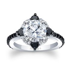 This unique black and white diamond halo engagement ring features a prong set round diamond center embellished with black and white diamond melee for a twist on the traditional halo ring. The narrow shank is adorned with shared prong set black diamonds for an elegant finish.<br /> <br /> Also available in rose, yellow gold, 18k and Platinum.