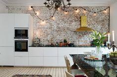 Se et spændende køkken med moderne elementer kombineret med rå vægge, messing- og marmordetaljer og personlige indretningsdetaljer