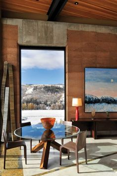 A Modern Rammed Earth House in Wyoming: A mountain view painting brings the outdoor landscape inside.
