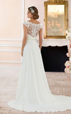 This off the shoulder lace back wedding dress from Stella York features a mix of classic lace and whisper soft chiffon that was made for walking down the aisle! With a bateau lace neckline that sweeps into an off the shoulder cap sleeve, this simple column silhouette is given a traditional twist. The lace continues over the bodice and just below a natural waistline, finishing in a scalloped edge under a sparkling detachable Diamante belt. The elegant chiffon train is complemented by an…