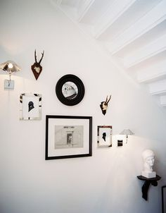 Antlers, prints, sconces, and a convex mirror mingle perfectly in this stairwell in Germany's Heidelberg Suites