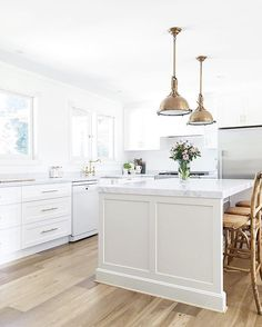 white kitchen + brass pendants + wood flooring