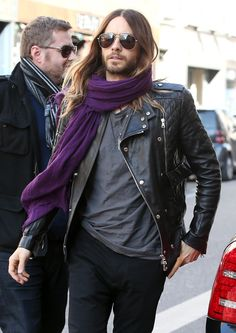 Jared Leto wearing a black quilted motorcycle jacket with a purple scarf
