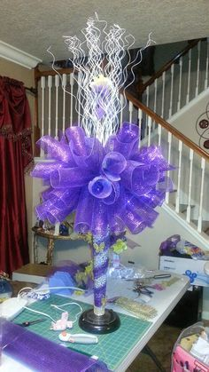 Niece's quinceanera large centerpiece using purple mesh, silver sticks and silver pearls strings inside. A light at the bottom and light on top. Plus yellow butterflies around the vase. I think they came out very lovely