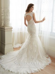 Sophia Tolli - Y11643 – Daria - Fiesta tulle over point d'esprit fit and flare wedding gown with slight lace cap sleeves, tip-of-the-shoulder plunging V-neckline with modesty panel, hand-beaded lace appliqué bodice with beaded midriff trim and dropped waist, semi sheer back bodice with keyhole and back corset, appliqués cascade down skirt, scalloped hem lace, chapel length train.Also available with a back zipper as style Y11643ZB.  Sizes: 0 – 28  Colors: Almond, Ivory, White