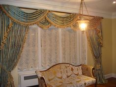 """Formal open neck swags and drapery panels with tassel trim on 2"""" brass pole over austrian shades"""