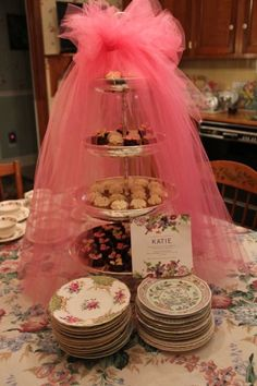 Tasty treats for a bridal shower served in a tiered draped with a wedding veil.  See more bridal shower decorations and party ideas at www.one-stop-party-ideas.com