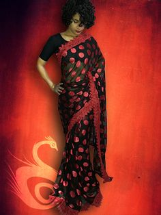 Make a distinct style statement wearing this black saree with red polka dots. This saree will give you a retro look with a touch of modernity. Look gorgeously charming at the next social do wearing this beautiful saree. Made from georgette, this saree has beautiful red polka dot and red lace border all over the saree.