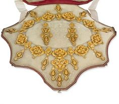 AN EARLY 19TH CENTURY GOLD DEMI-PARURE  The necklace composed of ten quatrefoil panels interspersed with trefoil links suspending oval-shaped pendants with palmette terminals and hinged foliate drop centres, the front with more elaborate pendant of girandole design, matching ear pendants en suite, circa 1840, necklace 43.0 cm long, ear pendants 6.5 cm long, with French assay mark for gold, in original red leather fitted case