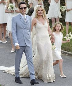 Kate Moss wed The Kills rockstar Jamie Hince at a village church in Cotswolds in a sequined John Galliano dress and Manolo Blahnik heels with blue lining, while the groom wore an Yves Saint Laurent suit, and Kate's daughter Lila Grace wore a Stella McCartney dress.