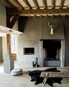 Raw Cement Plastered Walls, and Rough Hewn Timbers create a Modern and Masculine Living Room.