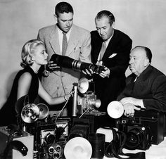 Grace Kelly, James Stewart and Alfred Hitchcock, the stars and director of Rear Window, being shown press photography equipment by L.A. Times photographer Phil Bath. Los Angeles, California. August 10th, 1954