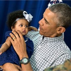 President Barack Obama holds a young girl while meeting with Marine personnel and their families at Marine Corps Base Hawaii on Christmas Day, Dec. (Official White House Photo by Pete Souza)