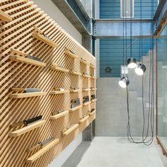 Sliding glass doors enclose a grid-like display of handmade knifes inside Japanese company Tadafusa's store by Tokyo designer Yusuke Seki