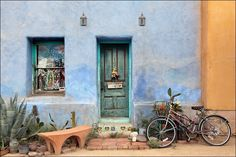 Photograph of colorful American Southwest urban scene with green wood door, bike, cactus and blue adobe wall. Wall décor photography for over your couch or home artwork decorating needs. Image title: Parking Close to Home This fine art image is from my photography series of colorful Southwest doors and was taken in the barrio area of Tucson, Arizona. These buildings are over 100 years old and the adobe walls are very thick to keep the buildings cool from the desert heat. All photographs…