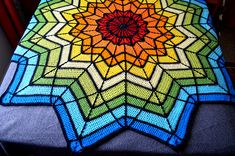 Free on Ravelry - I love this version, she used surface crochet to add the black lines after completing the blanket.  Beautiful stained glass look.