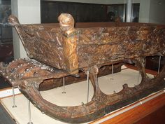 """Viking sled """"After some years as a sea-going vessel the Oseberg ship was finally laid to rest as a grave ship for a wealthy woman of high ranking. This woman received grace gifts for her journey to the realm of the dead, which included three highly decorated sleds and one sled of a simpler design (not displayed). The three highly decorated sleds were constructed in the same way: a separate upper frame was originally tied to the chassis with rope. The corner posts, shaped as animal heads, b"""