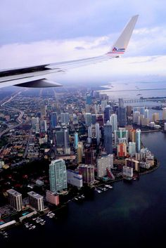 view of miami from the airplaine, ocean, skyline, tall buildings, clouds.