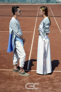 Lookbook:  Him: Blue and grey jacket. White pants Her: White top, grey bomber jacket, maxi white skirt. Tennis court, sport, sportswear, fitness, trends, unisex, campaign photos. Order via facebook, pm or e-mail.