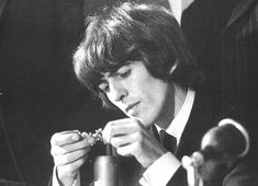 """thateventuality: """" Scan - George Harrison inspects his newly awarded MBE, 26 October 1965. Scanned from The Beatles Unseen Archives. Photo © Associated Newspapers Ltd. """""""