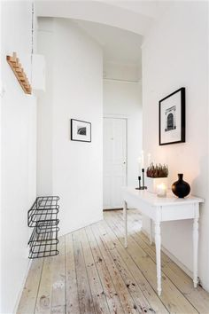 A wonderful hallway with a rough wood floor and table with art and flowers and candles.   Very lovely moment.