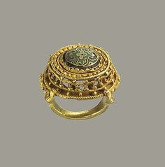 10th-11th century, Germany. Gold with cloisonné enamel. The ring is one of the most opulent and technically complex extant gold rings from the early Middle Ages. At the center is an elliptical flower form in gold cloisonné enamel. The flower's central element is a cruciform shape in white enamel framed by a greenish field with four crescent-shaped petals in bluish glass. Supporting the enamel is an elliptical hoop with arcades of twisted wire on the inside and the outside.