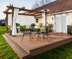 Breathtaking Backyard Before-and-Afters lovely wood deck with pergola on the far side attached to the back of a ranch style house. white curtains hang on either side of the pergola. outdoor furniture and potted plants rest on the deck. Deck With Pergola, Outdoor Pergola, Pergola Ideas, Pergola Kits, Cheap Pergola, Patio Ideas, Pergola Roof, White Pergola, Small Pergola